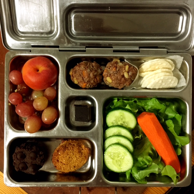 healthy lunch box, organic apricot, organic sulphite free grapes, lamb and cumin meatballs, organic rice crackers, salad, apricot and ginger cookie, chocolate zucchini mini muffin.